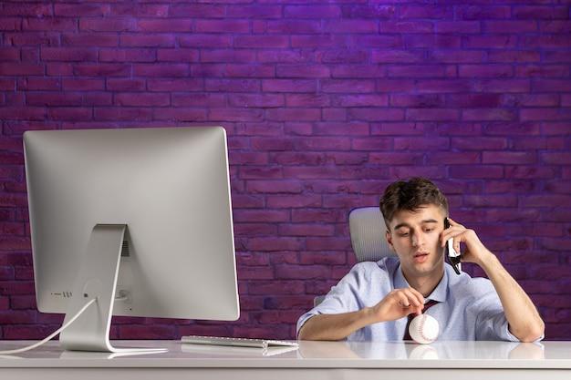 Trabalhador de escritório com vista frontal atrás de uma mesa de escritório segurando uma bola de beisebol e falando ao telefone