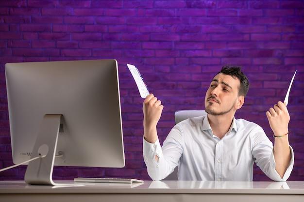 Trabalhador de escritório com vista frontal sentado atrás de seu local de trabalho e segurando ingressos