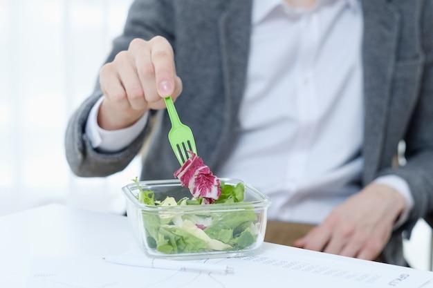 Trabalhador de escritório comendo salada de baixa caloria.