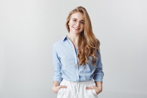 Trabalhador de escritório criativo relaxante após um longo dia de trabalho. mulher bonita, positiva, com cabelo loiro e blusa azul, segurando as mãos nos bolsos e sorrindo, expressando confiança sobre a parede cinza