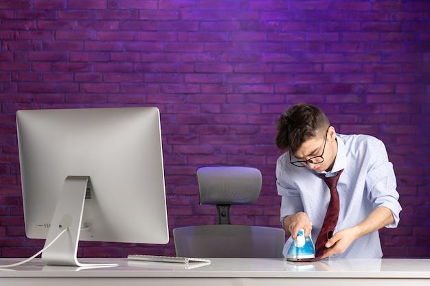 Trabalhador de escritório de frente atrás da mesa passando a gravata