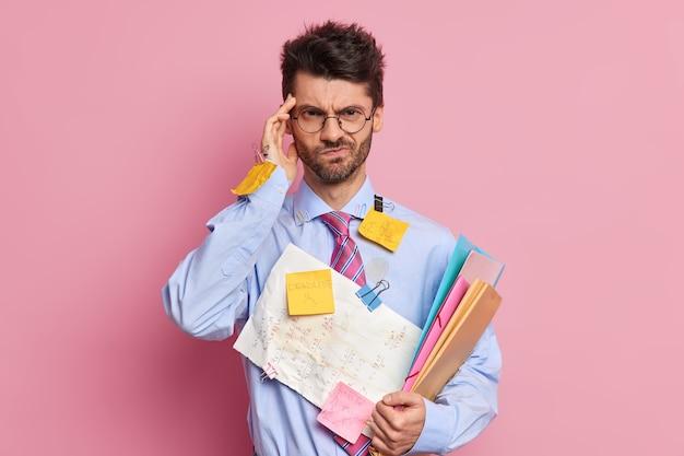 Trabalhador de escritório descontente e frustrado com dor de cabeça mantém a mão no templo parece descontente com a câmera cansado por causa de poses de papelada