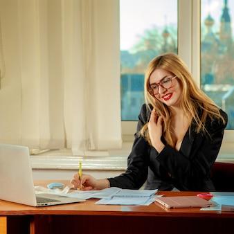 Trabalhador de escritório escreve o jornal e fala ao telefone. conceito de negócios