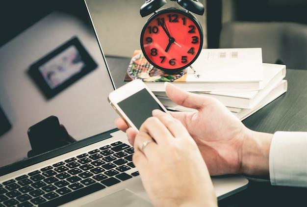 Trabalhador de escritório está segurando uma tela do smartphone em branco no escritório de cena de manhã