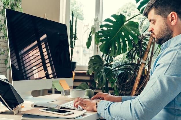 Trabalhador de escritório fazendo seu trabalho sentado à mesa de trabalho com um computador