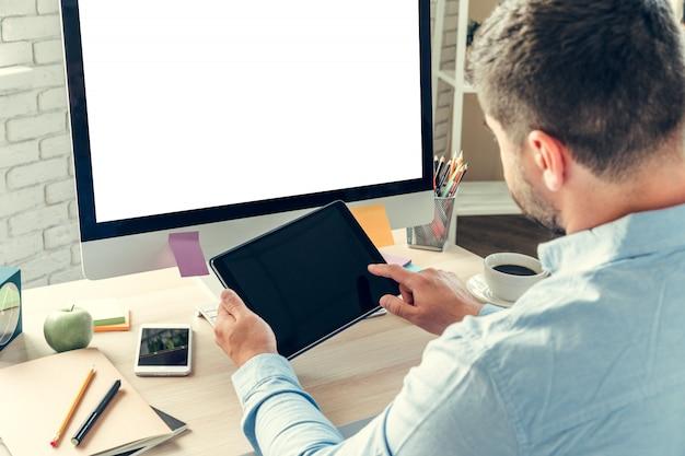 Trabalhador de escritório, fazendo seu trabalho, sentado à sua mesa de trabalho com um computador