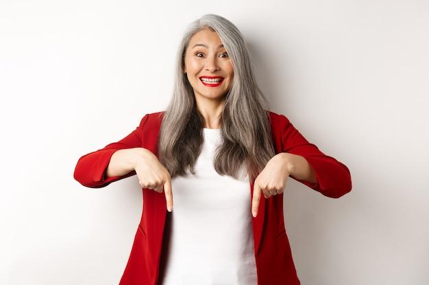 Trabalhador de escritório feminino asiático alegre apontando os dedos para baixo, sorrindo feliz, mostrando a oferta promocional, fundo branco.