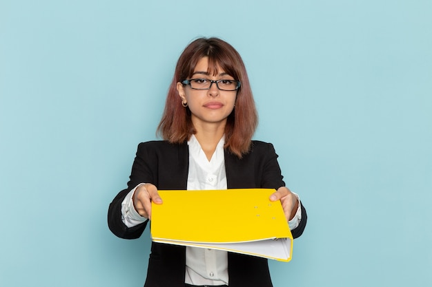 Trabalhador de escritório feminino com vista frontal segurando uma pasta amarela na superfície azul