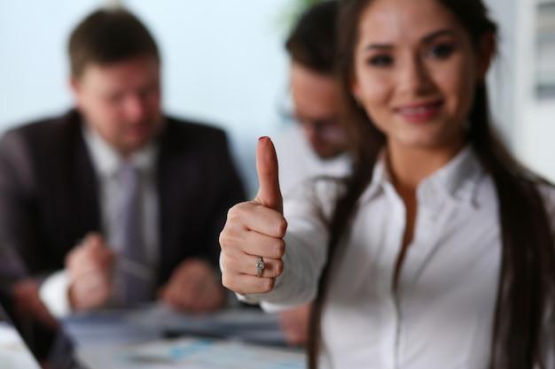Trabalhador de escritório feminino dando polegares para cima e sorrindo