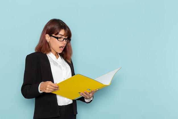 Trabalhador de escritório feminino de vista frontal lendo documento amarelo na superfície azul