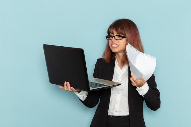 Trabalhador de escritório feminino em terno estrito segurando usando laptop na superfície azul