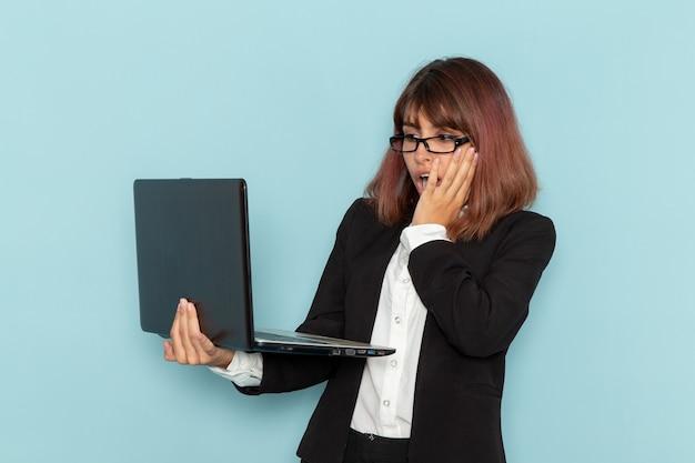 Trabalhador de escritório feminino em terno estrito, vista frontal, usando seu laptop em uma superfície azul-clara