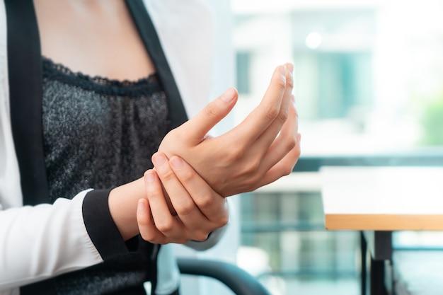 Trabalhador de escritório feminino está tendo lesão de síndrome de escritório em seu pulso