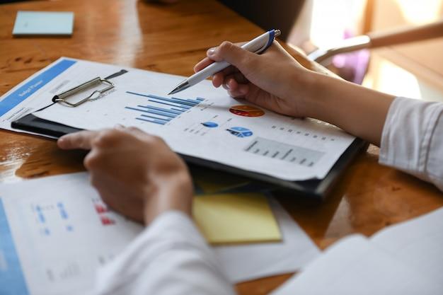 Trabalhador de escritório feminino segurando a folha de dados de gráficos. ela apontou a caneta em gráficos para analisar os dados.