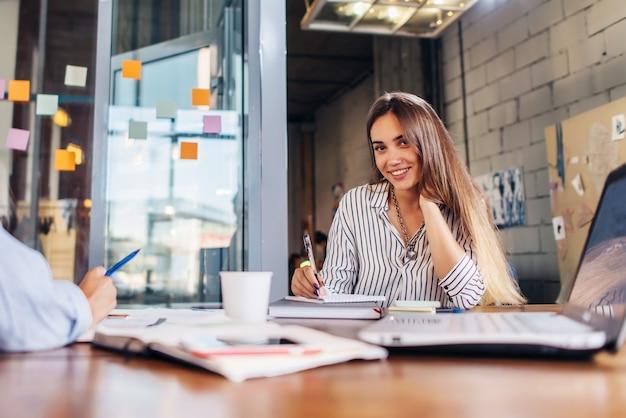 Trabalhador de escritório feminino sorridente, olhando para a câmera, sentado na sala de conferências durante a reunião