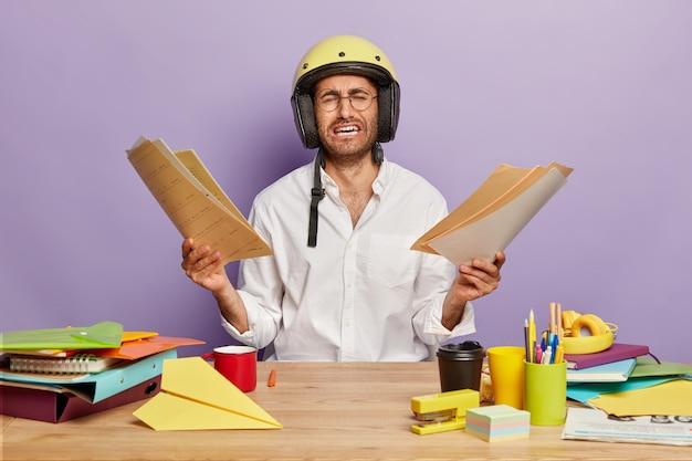 Trabalhador de escritório frustrado e sobrecarregado de trabalho segura papéis com as duas mãos, chora de desespero, usa óculos, capacete de proteção, posa na mesa