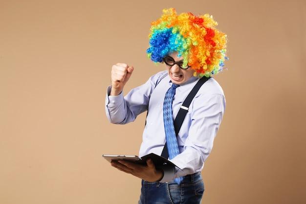 Trabalhador de escritório furioso dando socos no tablet enquanto usa peruca de palhaço
