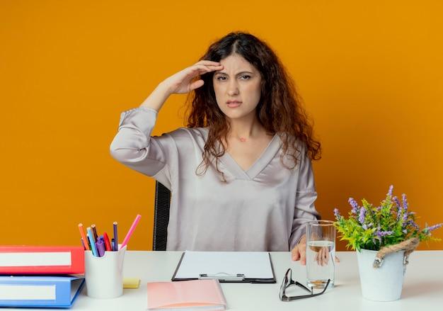 Trabalhador de escritório jovem bonita e desagradável, sentado à mesa com ferramentas de escritório, colocando a mão na testa isolada em laranja