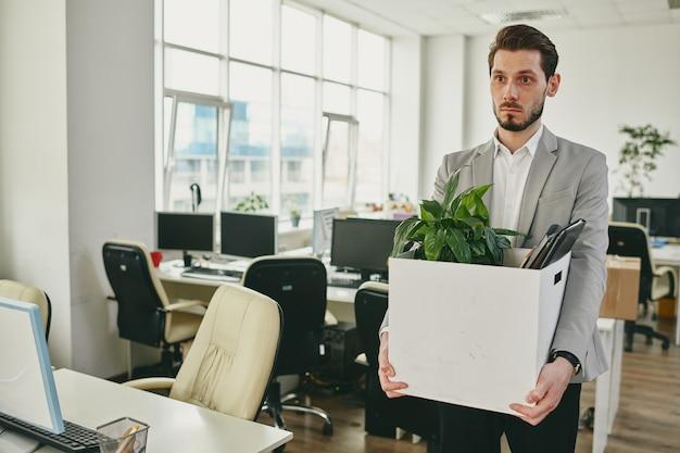 Trabalhador de escritório jovem infeliz carregando uma caixa com plantas verdes, documentos e outros suprimentos ao deixar seu local de trabalho após a quarentena