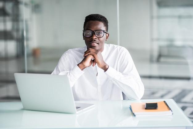Trabalhador de escritório jovem trabalhador positivo positivo, sentado na mesa em frente ao laptop aberto
