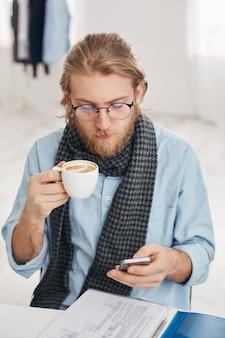 Trabalhador de escritório masculino barbudo em óculos redondos, vestido com camisa azul e cachecol, rodeado de papéis e documentos, recebe mensagem de negócios no smartphone, tipos de resposta, bebe café.