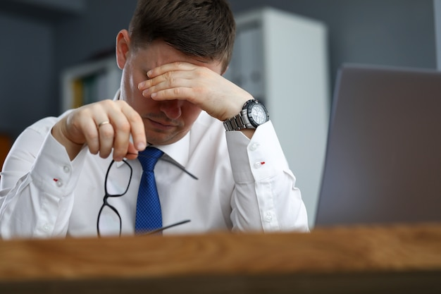 Trabalhador de escritório masculino cansado sentado na mesa de descanso. o corpo não é capaz de funcionar sem descanso, nutrição e atividade física adequados. trabalho ininterrupto e sem interrupção antes do projeto final