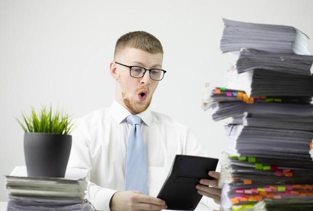Trabalhador de escritório masculino chocado com papéis e calculadora contando dinheiro - orçamento