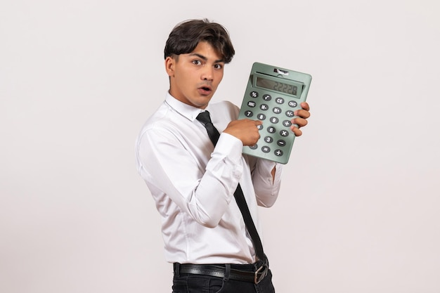 Trabalhador de escritório masculino com vista frontal segurando calculadora na parede branca.