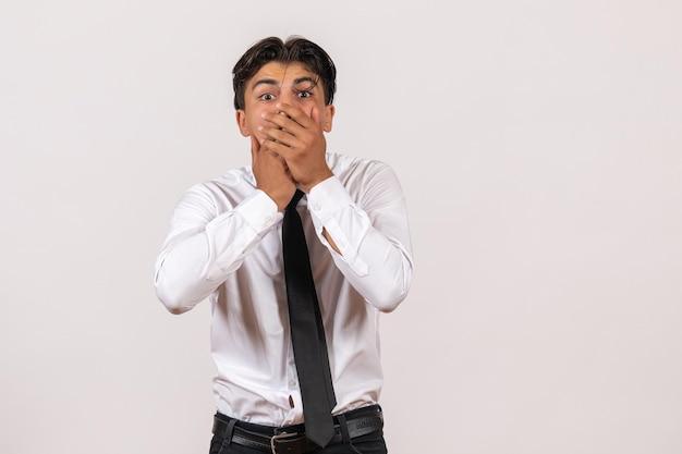 Trabalhador de escritório masculino de vista frontal com rosto chocado em uma parede branca.