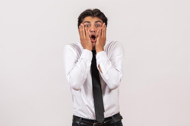 Trabalhador de escritório masculino de vista frontal com rosto nervoso na parede branca.