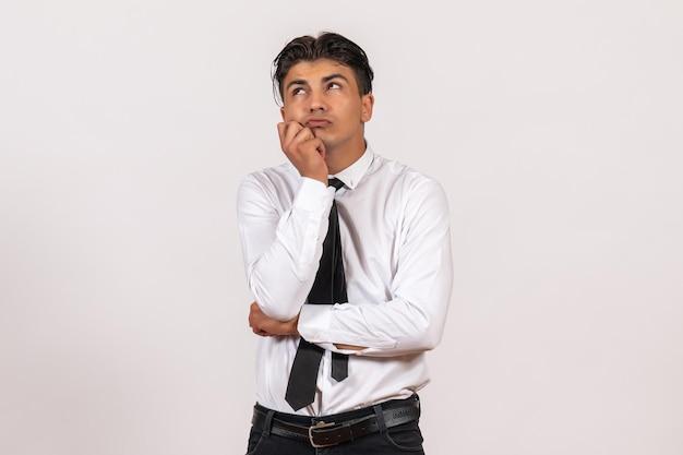 Trabalhador de escritório masculino de vista frontal pensando na parede branca, trabalho, trabalho masculino, negócio