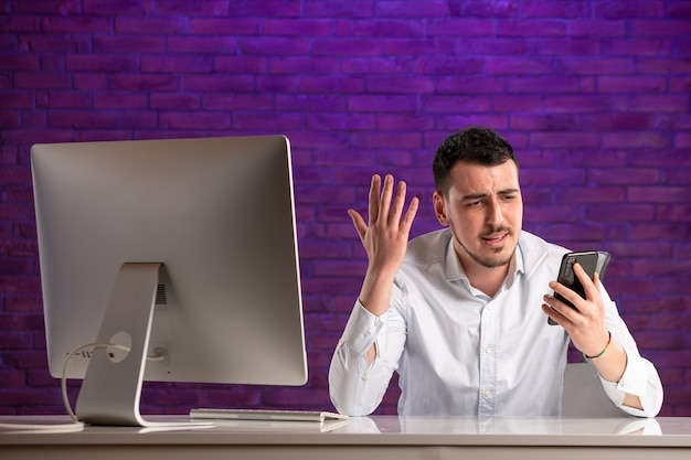 Trabalhador de escritório masculino sentado atrás de seu local de trabalho, conversando