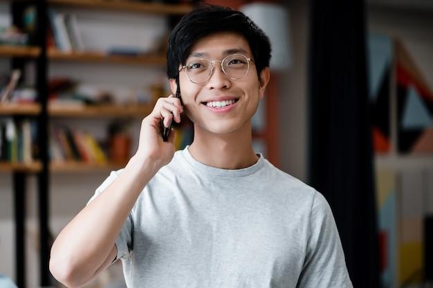 Trabalhador de escritório milenar asiático sorridente