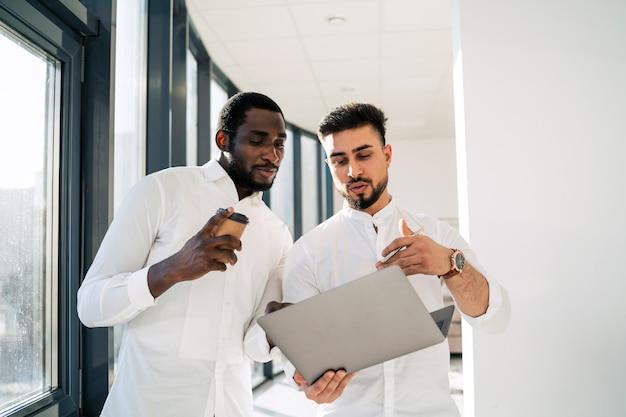 Trabalhador de escritório mostrando ao chefe um relatório no laptop