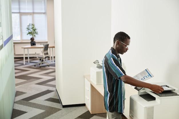 Trabalhador de escritório negro sério fazendo cópias de gráficos e relatórios de negócios na copiadora