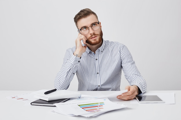 Trabalhador de escritório ocupado liga para parceiro de negócios para discutir reunião futura