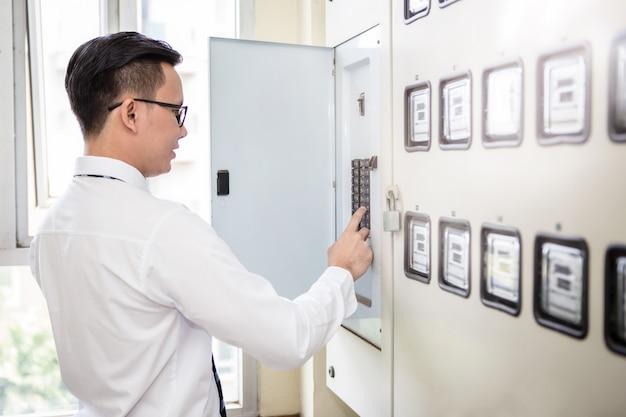 Trabalhador de escritório olhando e verificando o painel de controle de eletricidade no prédio de escritórios