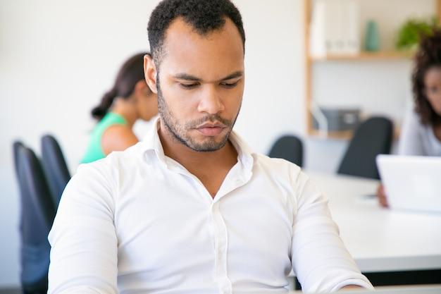 Trabalhador de escritório pensativo, sentado à mesa e olhando para laptop