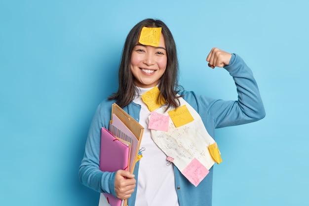 Trabalhador de escritório positivo levanta o braço e mostra que os músculos se sentem fortes.