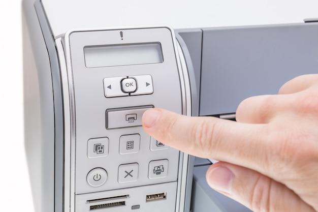 Trabalhador de escritório pressiona o botão da impressora. fechar-se.
