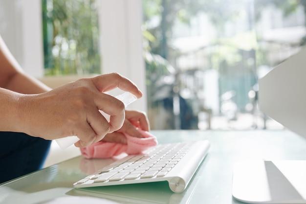 Trabalhador de escritório pulverizando spray antibacteriano no teclado