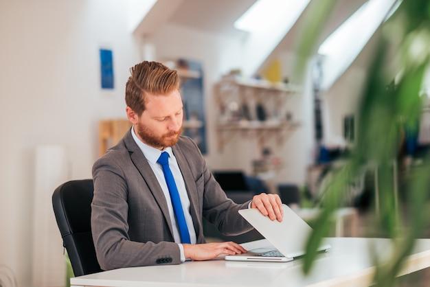 Trabalhador de escritório que começa o trabalho no portátil no escritório moderno.