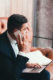 Trabalhador de escritório usando laptop e smartphone.