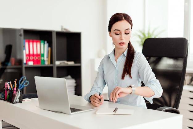 Trabalhador de escritório, verificando o tempo no relógio no escritório
