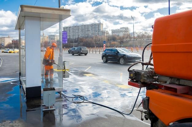 Trabalhador de estrada, limpeza da rua da cidade com lavadora de alta pressão, moscou, rússia
