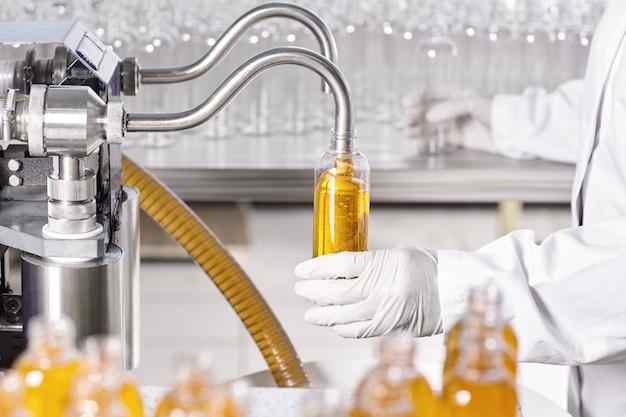Trabalhador de fábrica com vestido branco e luvas de borracha segurando uma garrafa de plástico