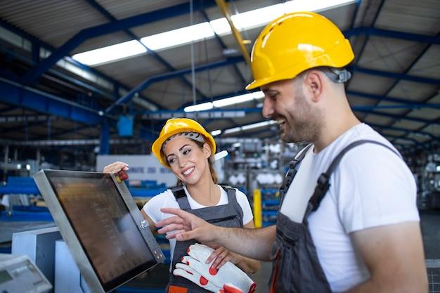 Trabalhador de fábrica explicando o trainee como operar uma máquina industrial usando um novo software em um computador com tela de toque