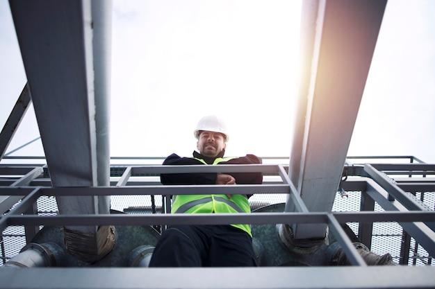 Trabalhador de fábrica industrial encostado na grade de construção metálica da planta de produção no pôr do sol.