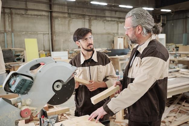 Trabalhador de fábrica maduro em roupas de trabalho olhando para um jovem colega enquanto o consultava sobre como usar a serra elétrica