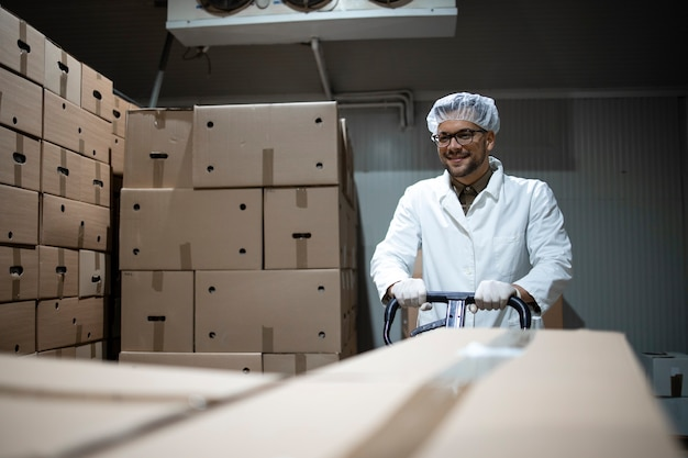 Trabalhador de fábrica movendo pacotes com alimentos orgânicos frescos em armazenamento refrigerado.